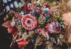 Autumn colors abound in this purple, blue and brown floral arrangement